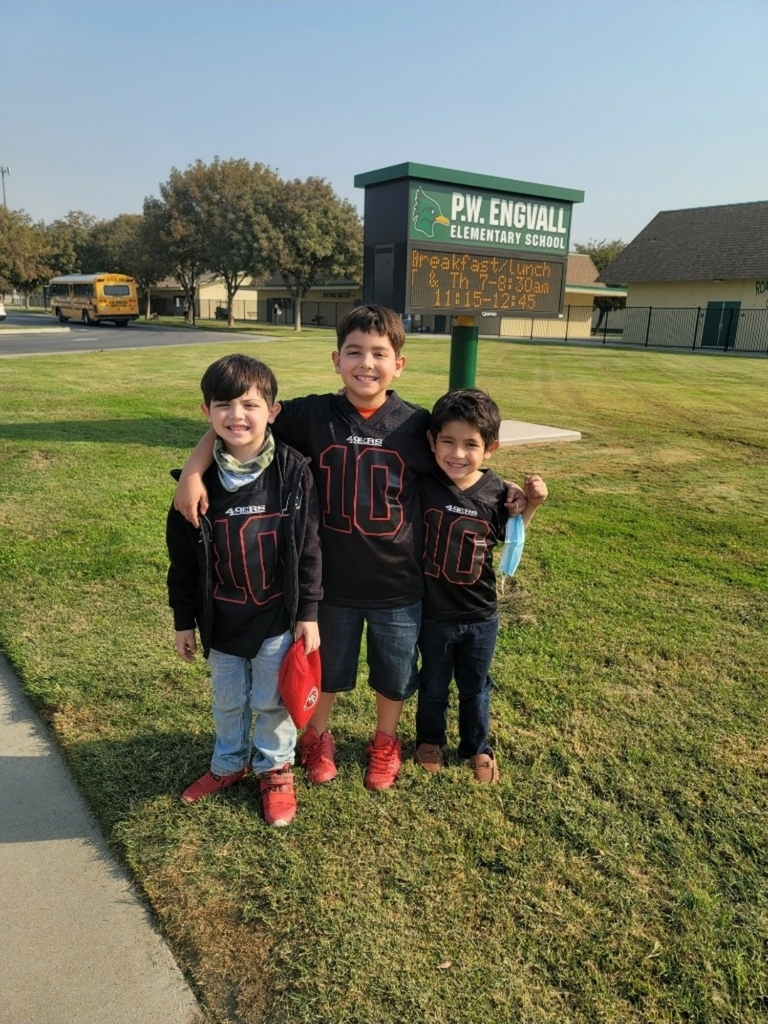three students standing for a picture.  They have on football  jerseys