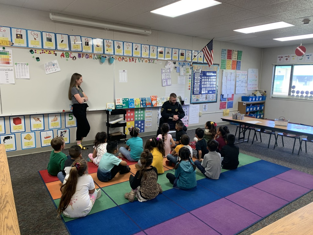 Police Officer reading to students in a classroom